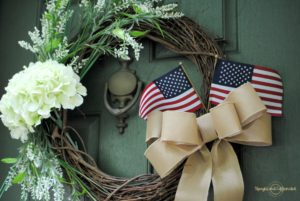 This DIY Spring Wreath easily transitioned to a beautiful simmer wreath with the addition of a burlap bow and a couple of American flags.